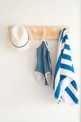 swimsuit and hat hanging on a coat rack