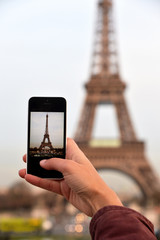Woman taking photos with a smartphone to the Eiffel Tower