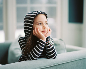 Cute young girl sitting in a chair looking out a window