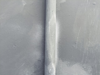 Detail of spray painted gutter pipe on building wall