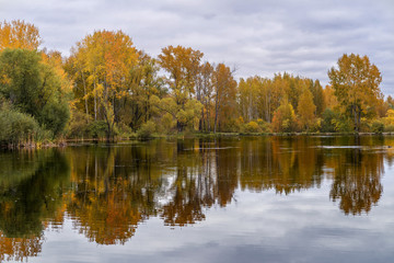 The lake, reflecting the cloudy sky and autumnal foliage trees