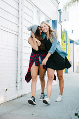 Two female friends walking down the sidewalk and having fun