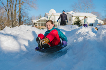 A girl sleds down a snowy residential slope.
