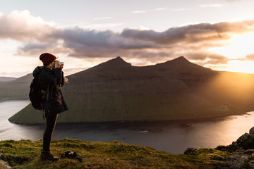 Woman Taking a Photo at a Mountain Overlook at Sunset