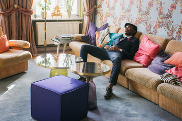 Fashionable Young Black Man Napping in Bright Living Room
