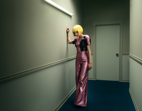 model wearing a wig in a hallway with green walls