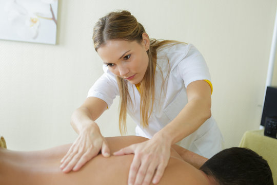 a beautiful masseuse applying a massage to a male client