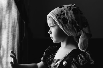 Little girl in pirate scarf looks out of a glass door.