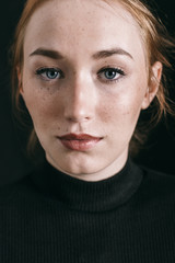 Closeup portrait of a ginger freckled woman on black.