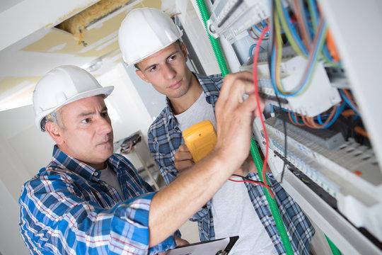 tutor instructing trainee electrician
