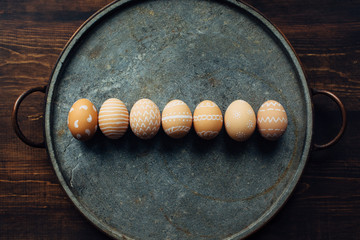 Seven decorated eggs aligned on a stone plate
