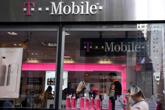 A pedestrian uses her smart phone as she passes a T-Mobile retail store in New York City