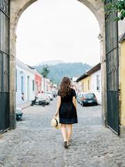 Woman walking down cobblestone street