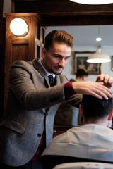 A gentleman barber inspects a client's hair before a cut.