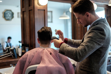 A gentleman barber uses a comb & electric clippers to cut a clients hair.