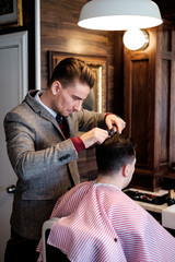 A gentleman barber focuses intently while cutting a client's hair.