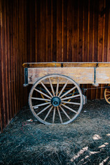 A old carriage against a stained wood wall