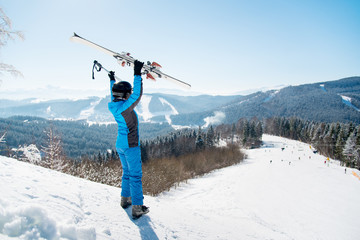Rearview full length shot of a woman skier standing on a slope at ski resort, raising her skis up in victorious gesture copyspace success achievement concept