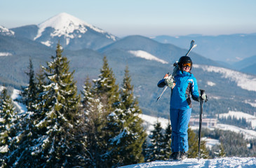 Happy female skier standing on top of a mountain with skis on her shoulder stunning scenery. Mountains, forests on the background copyspace winter snow mountains nature recreation resort