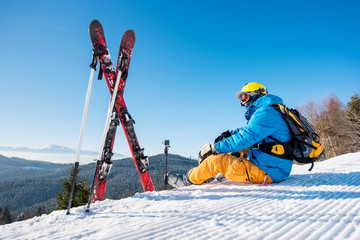 Shot of a skier sitting on slope near his skiing equipment relaxing enjoying beautiful snowy mountains view people living enjoyment recreation travelling riding winter resort