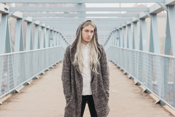 Handsome male model with long blond hair on the bridge