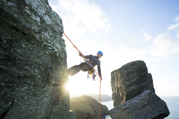 Teenage boy, rock climbing.