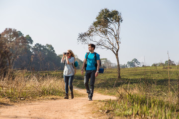Couple walking with backpacks outdoors - adventure, travel, tourism
