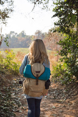 Young woman backpacker from behind