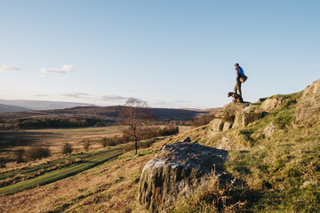 Male and his dog on a hilltop at sunset. Upper Padley, Derbyshire, UK.
