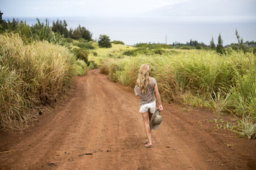 Woman walking down a dirt trail in Maui, Hawaii