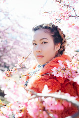 Outdoor Portrait of Pretty Young Japanese Woman Standing Next to Blossoming Sakura Tree