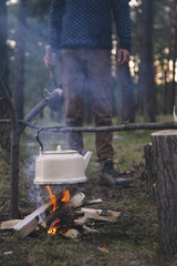 Old kettle hanging on branch over campfire in the forest
