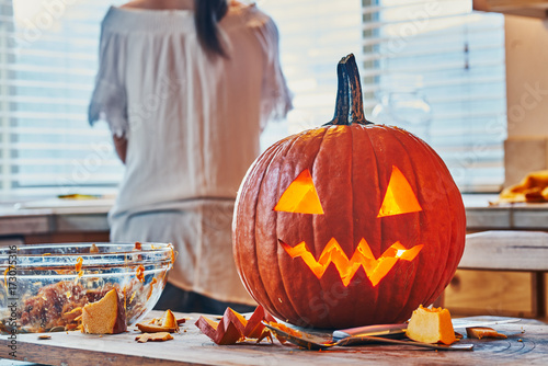 cleaning up after making jack o lantern pumpkin for halloween on kitchen table