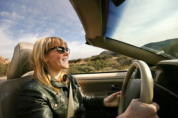 Excited young woman driving a convertible