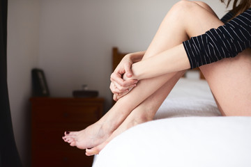 Woman embracing her legs while sitting on bed