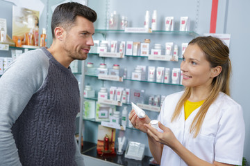 pretty pharmacist counseling customer about drugs usage