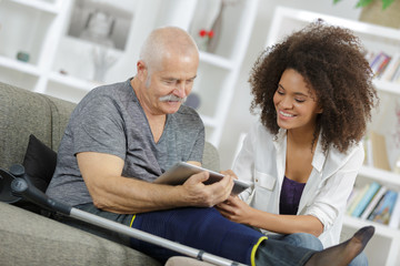 young woman and senior man chating with family using tablet