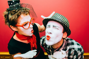 two mimes posing against a red wall background