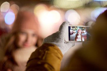 hand with woman christmas picture on smartphone