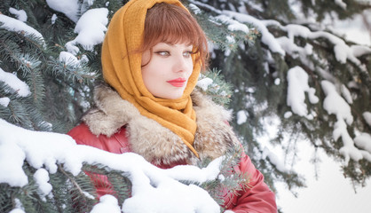 Portrait of a woman in a winter snowy day. In a scarf with red lips in a snowy forest in in Christmas trees.
