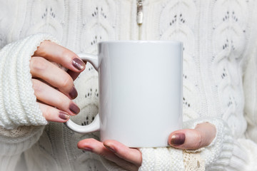 Woman holds white mug in hands. Design Mockup for winter holidays