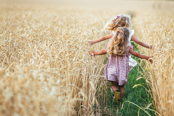 Emotional sisters run on the wheat field at sunset, the concept of freedom and childhood, lifestyle, pastel colors