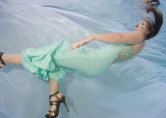 Brunette model wearing an aqua colored dress.