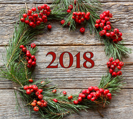 Christmas wreath of pine branches and red Rowan on wooden background. New year inscription 2018