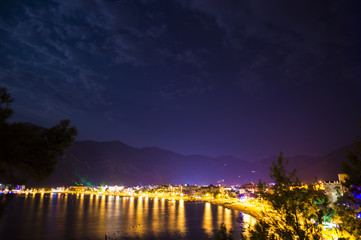 Evening view of the town of Icmeler. The bay is surrounded by mountains. Night life. Beach illuminated by evening lights
