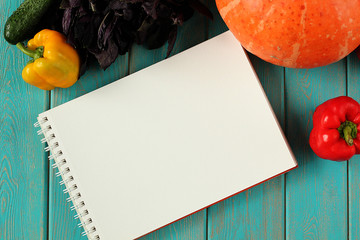 Note book and composition of vegetables on blue wooden desk.
