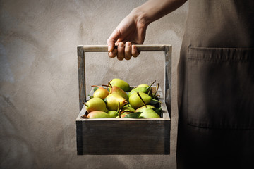 Woman holding wooden basket with ripe pears on light background