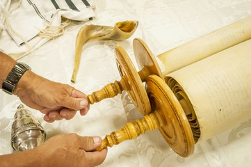 Hands of a Caucasian man holding the handles of the Torah scrolls.