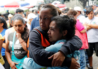 People attend a mass by priest David Gimenez along the street next to a collapsed building after an earthquake in Mexico City