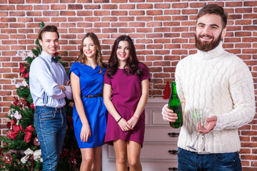 Christmas time with friends concept. Bearded man holding champaign and two glass.